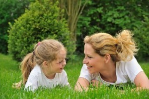young-mother-and-daughter-laying-on-the-grass